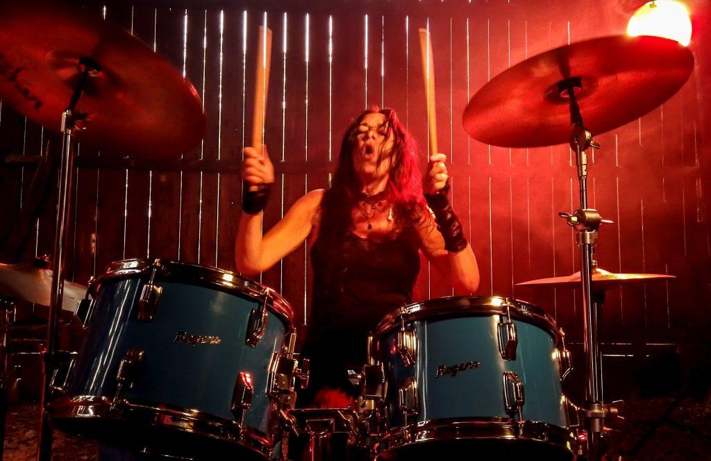 Nike Markelius spelar trummor i rökig klubbmiljö.