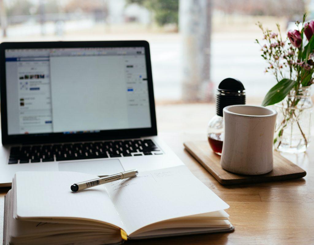 Laptop och öppen bok, kaffekopp
