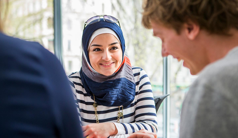 Ung kvinna i slöja ler. ABF Stockholm Komvux Liljeholmen.